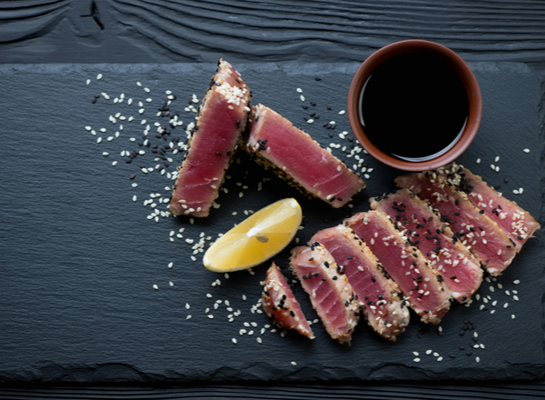 Stone slate tray with sliced tuna steak fried in sesame seeds.