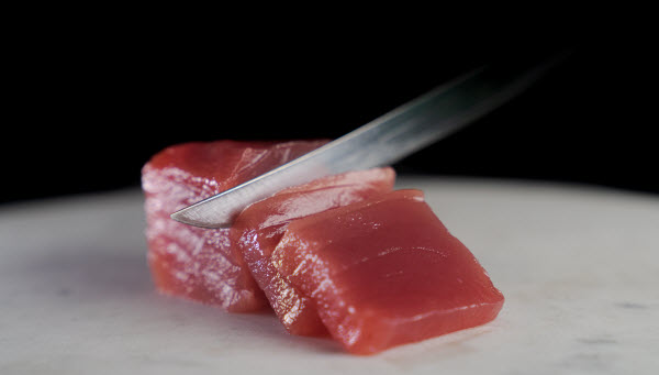 Knife slicing a tuna