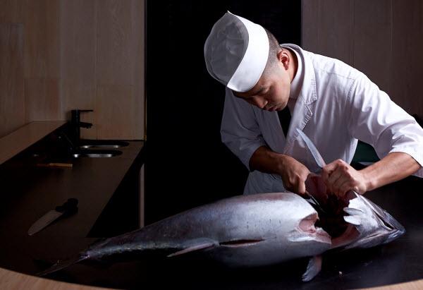 Chef cutting a big chunk of Tuna