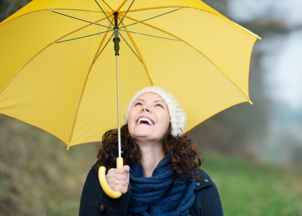 Happy young woman in winter clothes holding yellow umbrella